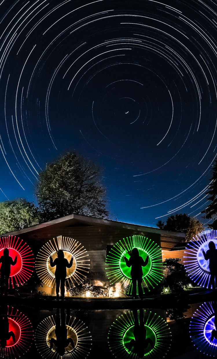 An artist captures himself spinning colored light bars under the night sky