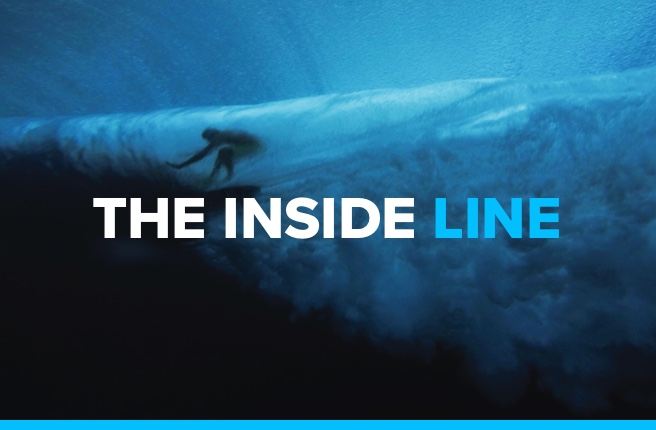 "A surfer in the barrel of a wave with ""The Inside Line"" on top of it."